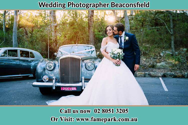 Bride kissed by Groom beside the bridal car Beaconsfield NSW 2015