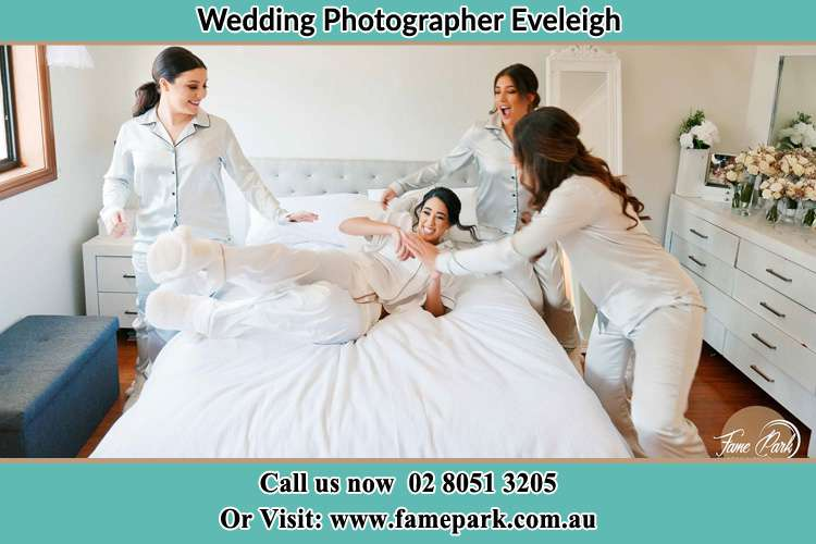 Bride laying in bed with her brides maids Eveleigh