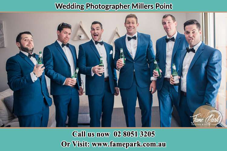 Groom and his secondary sponsors holding a bottle of beer Millers Point NSW 2000