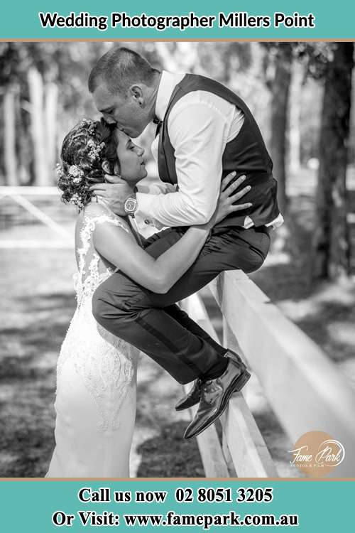 Groom kiss the Bride while sitting on the fence Millers Point NSW 2000