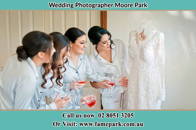 Bride looking at the wedding gown with her bride's maids Moore Park NSW 2021