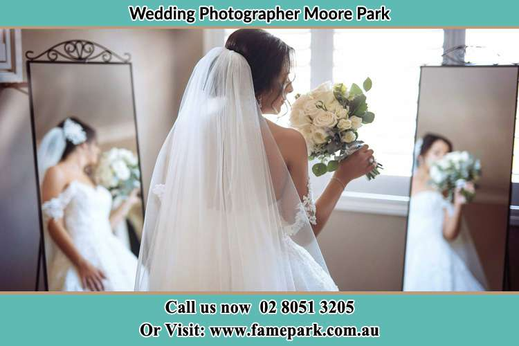 Bride looking at the mirror with bouquet of flowers Moore Park NSW 2021