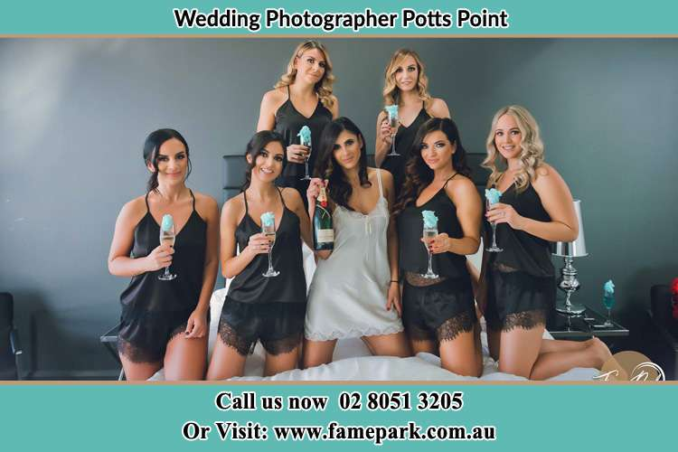 Bride and bride's maids holding wine in the bed Potts Point NSW 2011